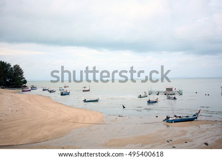 A scenery of a fisherman boat at the beach facing towards open sea with white cloud background