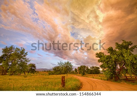 A scenic drive on a dirt country road in North Boulder County Colorado with a magical colorful view of the leading edge of a beautiful dramatic storm cloud front.  - stock photo