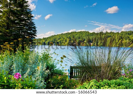 A scenic lake in the mountains. There is a bench and a flower garden in the foreground. - stock photo