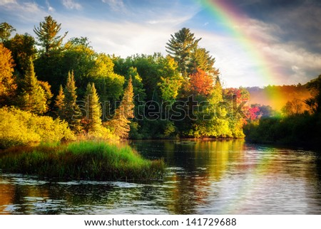 A scenic lake or river during a light rain displaying a rainbow in the mist on an autumn day close to sunrise or sunset. - stock photo