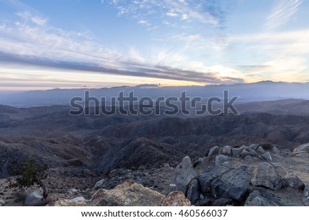 A scenic view of a large hilly terrain taken from an overlook during sunset in Joshua Tree National Park, California, USA