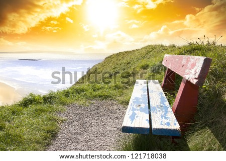 a scenic view of Ballybunion beach and Atlantic Ocean on a bright sunset evening from a bench - stock photo