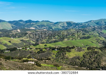 A scenic view of Carmel Valley, in Monterey County of central California, with rolling hills dotted with ranches and grass covered hills. - stock photo