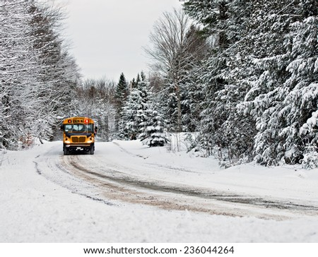 A school bus drives down a snow covered rural country road lined with snow covered trees after a snow storm during the winter season.  Series 1 of 3  - stock photo