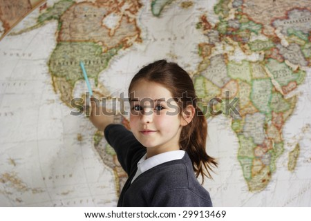 A school girl indicating the United States of America on a world map - stock photo