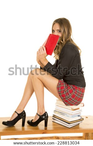 A school girl peeking over a book while she sits on books. - stock photo
