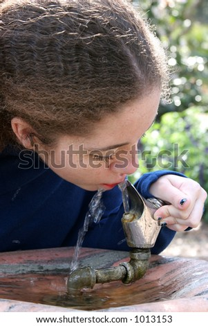 A school girl taking a drink of water on the playground. - stock photo
