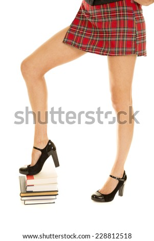 A school girl with her foot up on a stack of books. - stock photo
