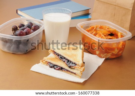 A school sack lunch with books, grapes, ravioli, and a peanut butter and jelly sandwich - stock photo