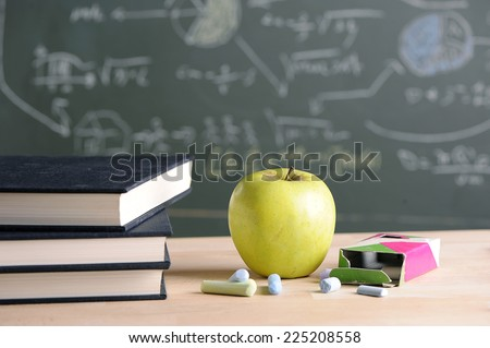 A school teacher's desk with stack of exercise books and apple in left frame. A blackboard in soft focus - stock photo