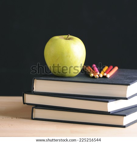 A school teacher's desk with stack of exercise books colored pencils and green apple. A  blackboard  - stock photo
