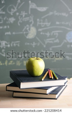 A school teacher's desk with stack of exercise books colored pencils and green apple. A green blackboard  - stock photo