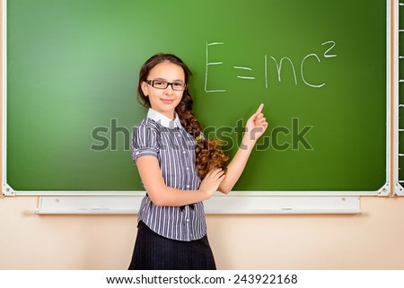 A schoolgirl in spectacles stands at the blackboard during a physics lesson. Education. - stock photo
