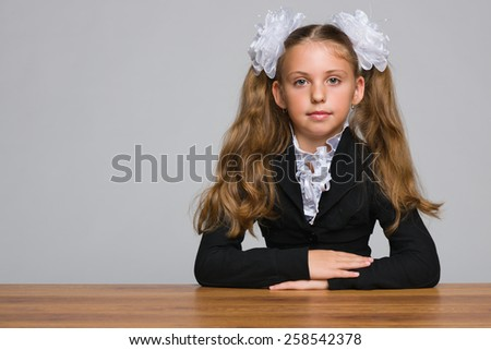 A schoolgirl sits at the desk against the gray background - stock photo