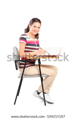 A schoolgirl sitting on a chair and writing down notes isolated on white background