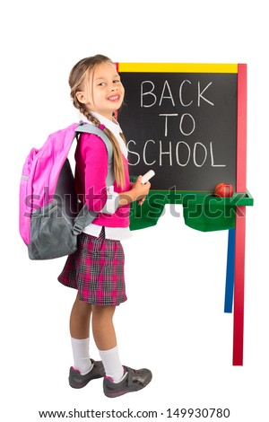 """A schoolgirl standing next to the blackboard with the """"Back to School"""" message on it, isolated - stock photo"""