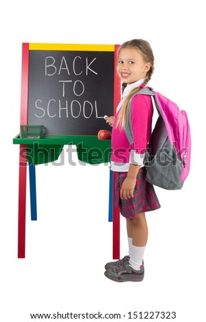 "A schoolgirl standing next to the blackboard with the ""Back to School"" message on it, isolated"