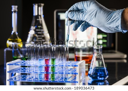 a scientist adding liquid to a test tube with beakers in the background