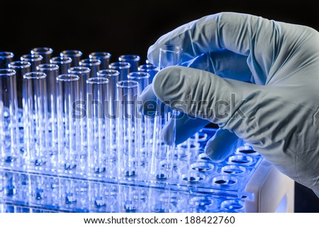 a scientist holding a test tube - stock photo