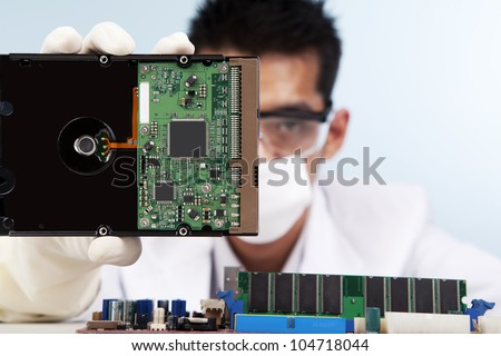 A scientist showing a computer hard disk shot in studio against blue background