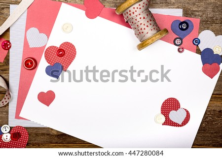 A scrapbooking themed background with cutout hearts, craft paper, ribbon and buttons. Space for your text - stock photo