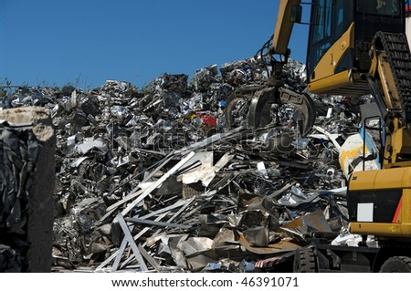 A scrapyard working with a grabber - stock photo