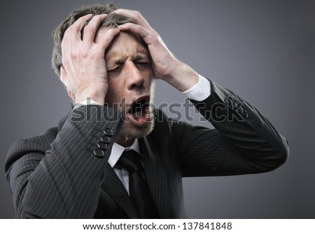 A screaming worried, depressed, and stressed out businessman holds his head - stock photo