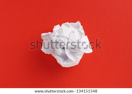 A scrunched up ball of white printing or writing paper in the center of a red paper background - stock photo