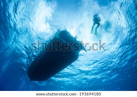 A scuba diver descends from a boat into the clear blue water of the Caribbean Sea. - stock photo