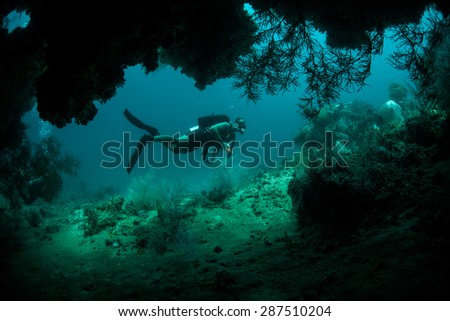 A scuba diver explores a cave found deep on a coral reef in Raja Ampat, Indonesia. This remote tropical area, found off the coast of Papua, harbors some of the Coral Triangle's most healthy reefs. - stock photo
