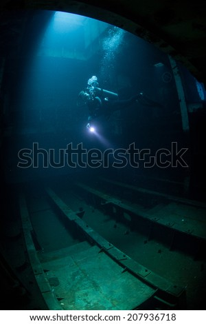 A scuba diver penetrates the interior of a famous shipwreck, the USS Kittewake, in Grand Cayman. Diving inside wrecks can be dangerous but this one has been made as safe as possible. - stock photo