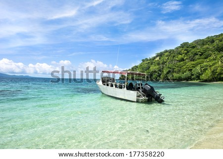 A scuba diving boat is anchored in a beautiful tropical bay of turquoise water and a bright, blue vibrant sky with patchy clouds. - stock photo
