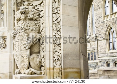 A sculpture of a lion holding the shield of Canada at the entrance of the Parliament buildings in Ottawa.
