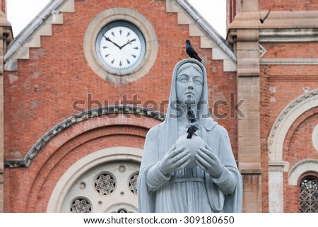 A sculpture of the Virgin Mary in front of the Notre-Dame Saigon Basilica in Ho Chi Minh City, Vietnam - stock photo