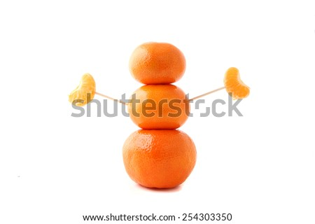 A sculpture representing a healthy person made of clementine oranges isolated over a white background. - stock photo