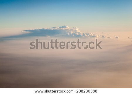 a sea of clouds seen from above while flying in a commercial airplane - stock photo