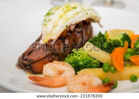 A seafood dinner of lobster tail, shrimp and vegetables - stock photo