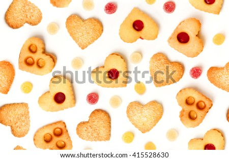 A seamless background pattern with heart-shaped tea cookies and gum drops on white - stock photo