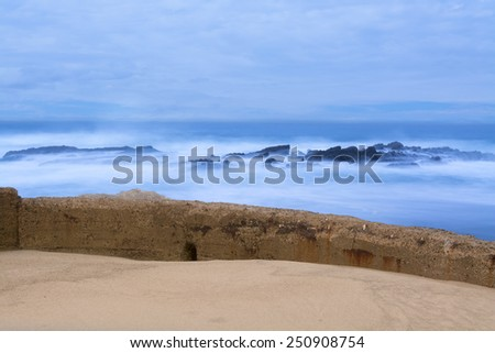 A seawall separates the rough ocean from a sandy beach during an early morning sunrise - stock photo