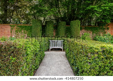 A secluded old English garden style park bench, is surrounded by lush green plants, vegetation, and shaded by a century old tree. In the background, an old brick English wall from the 20th century. - stock photo