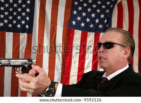 a Secret Service Agent points his weapon at a suspect - stock photo