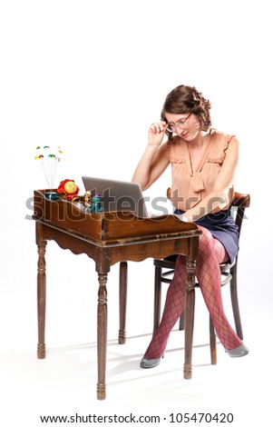 A secretary in vintage clothes at an antique desk works at a laptop. - stock photo