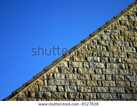 A section of limestone wall neatly diagonally dissecting a blue sky