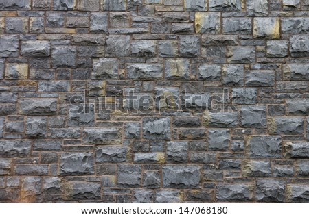 A section of wall made of grey cut stone