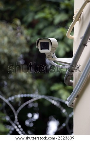 A security camera is watching over a secure area with razor wire in the background.