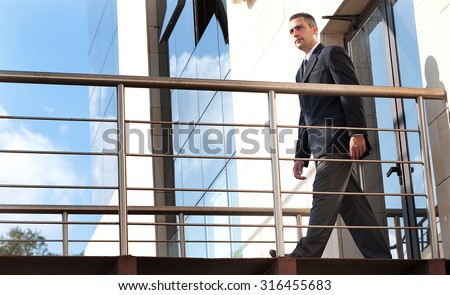 a security guard in do his patrol in  a outdoor corridor of a building