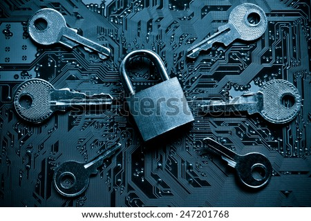 a security lock on a computer circuit board surrounded by keys / random password hacking concept - stock photo