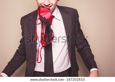A seductive businessman has a bra in his mouth - stock photo