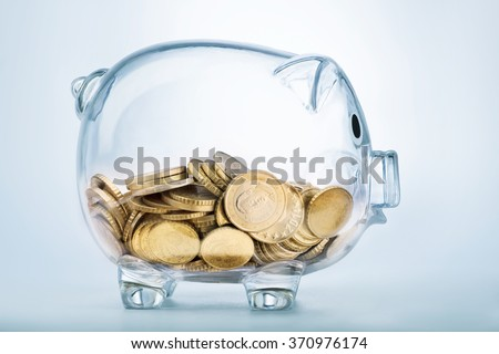A see through piggy bank with money coins  - stock photo