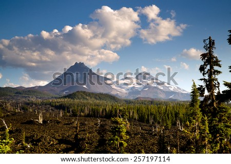 A seemingly endless field of lava leads out to the Sisters near Bend Oregon - stock photo